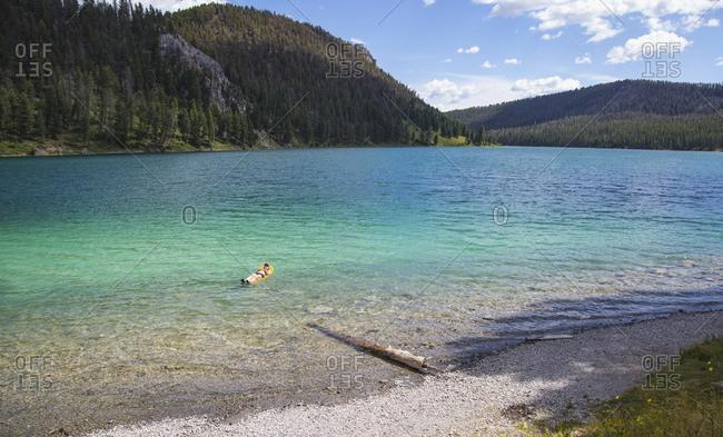 Woman floating in blue water in beautiful mountain lake