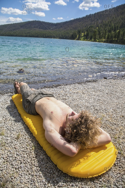 Man lounging in the sun on float at rocky lake beach