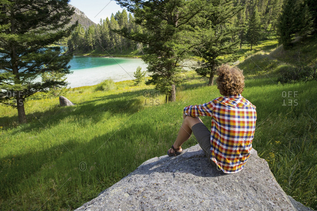 Man gazing at lake from rock