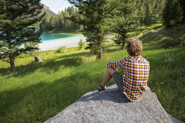 Man gazing at lake from rock