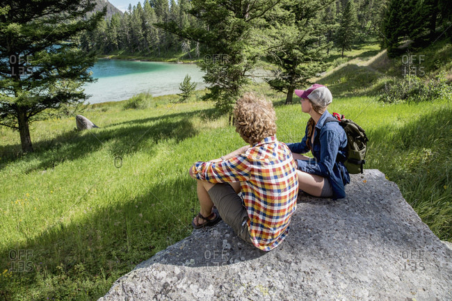 Young couple on rock gazing at lake
