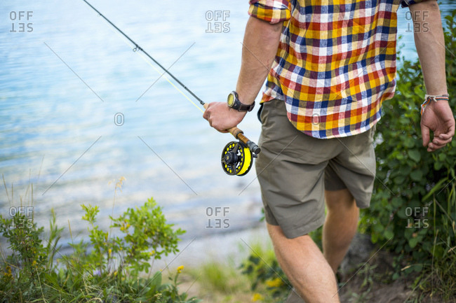 Man walking to water's edge with fishing pole