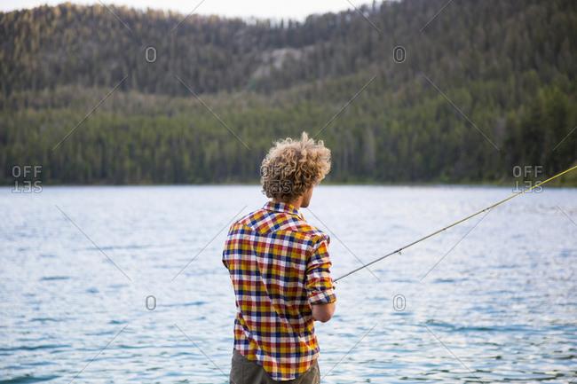 Back view of man in plaid shirt fishing at lake
