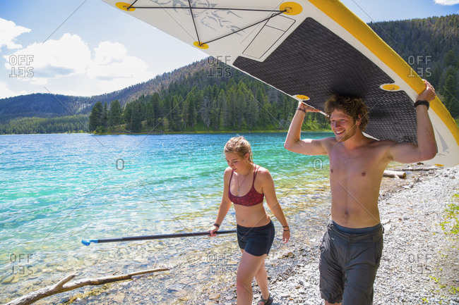 Man carrying paddleboard while walking with woman