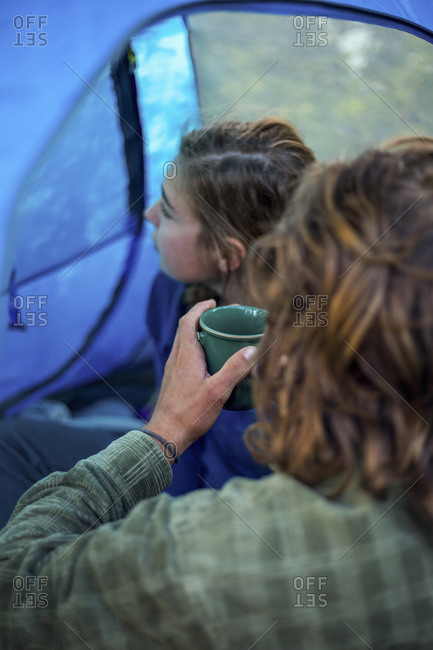 Man and woman drinking coffee in their tent
