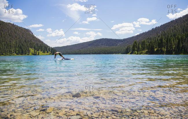 Man diving off paddleboard in mountain lake