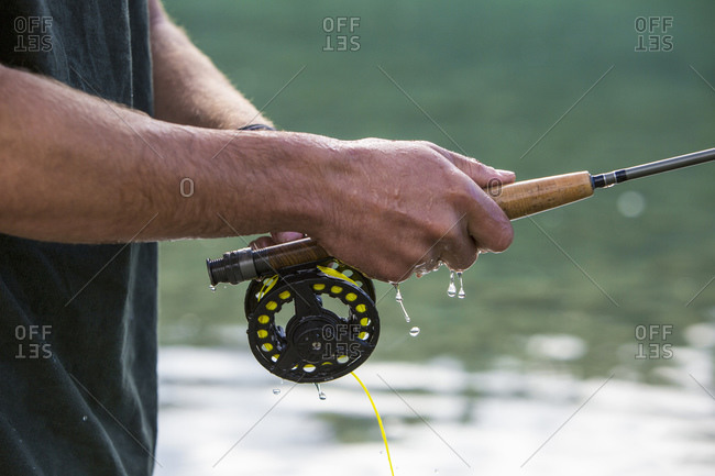 Water dripping from man's hand holding a fly fishing pole
