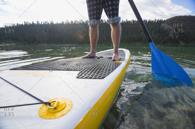 Close-up of man's feet on paddleboard
