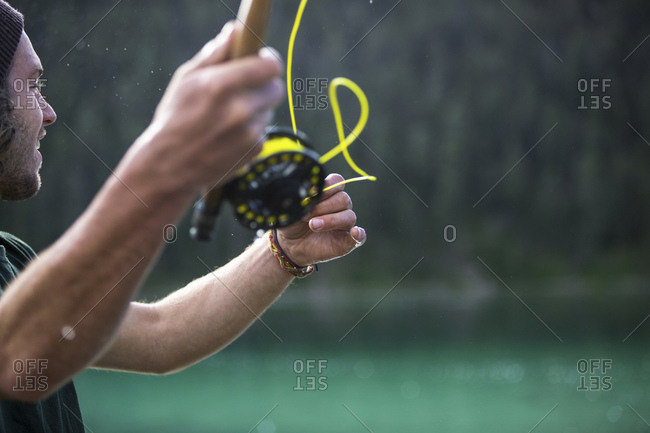 Man casting yellow fishing line from pole