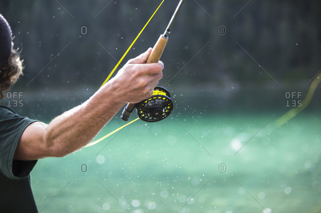 Back view of man's arm casting with a fly fishing pole