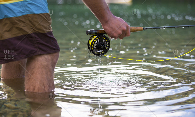 Man standing in knee-deep water with fishing pole