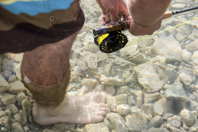 Elevated view of man's foot in a rocky lake as he fishes