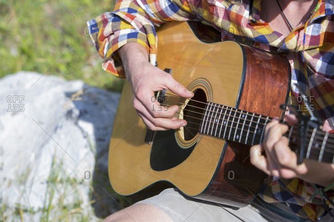 Man in plaid shirt playing acoustic guitar outdoors