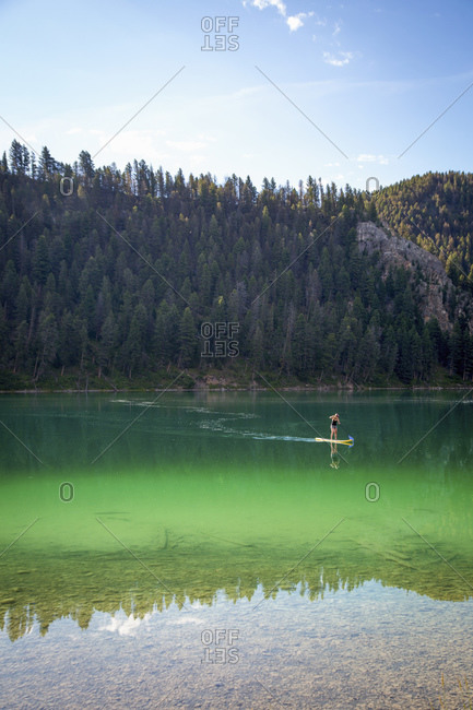 Woman paddleboarding across a lake