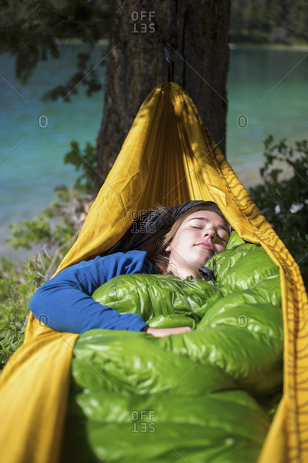 Woman sleeping in hammock at campsite