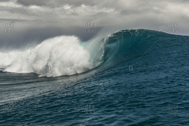 Tall breaking wave in the Pacific Ocean by Moorea Island, French Polynesia