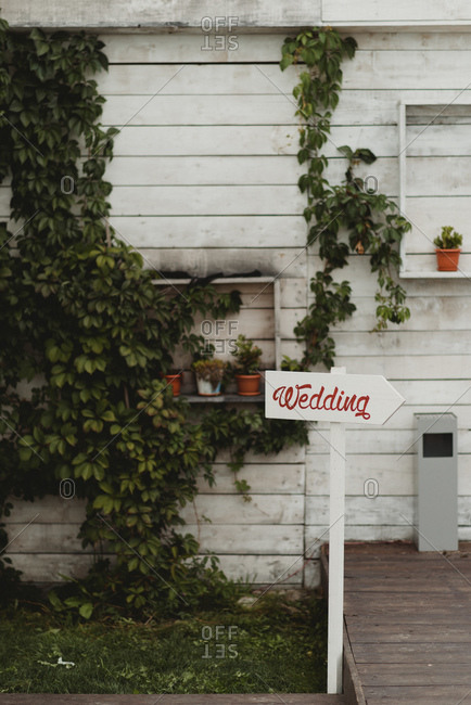 Wedding sign in front of a white clapboard building and green vines