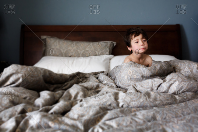 Little boy sitting up in a bed after waking up