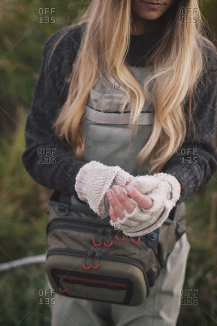 Woman with blonde hair wearing chest waders and fingerless wool mittens