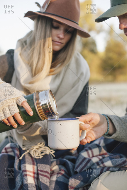 Woman pouring a hot drink from a vacuum flask into a cup on a winter picnic