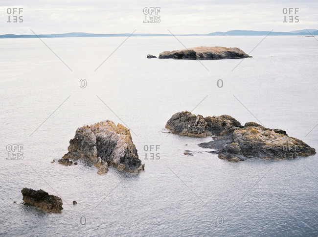 Rocky islands in a bay and distant mountains