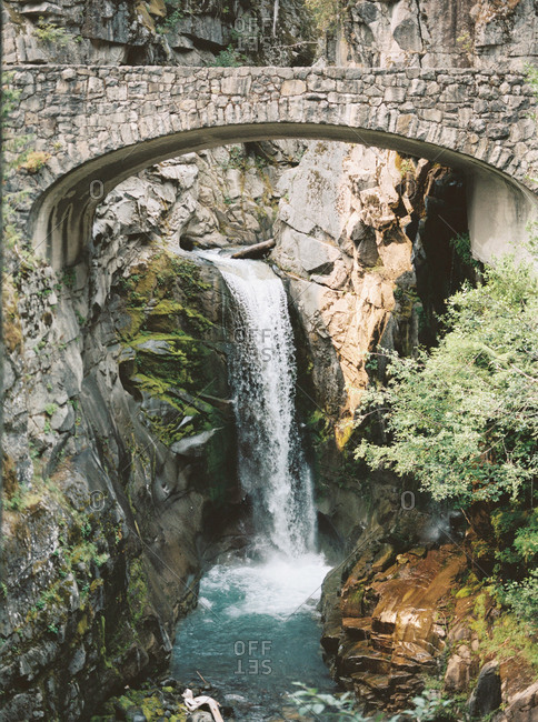 Arched stone bridge and a waterfall