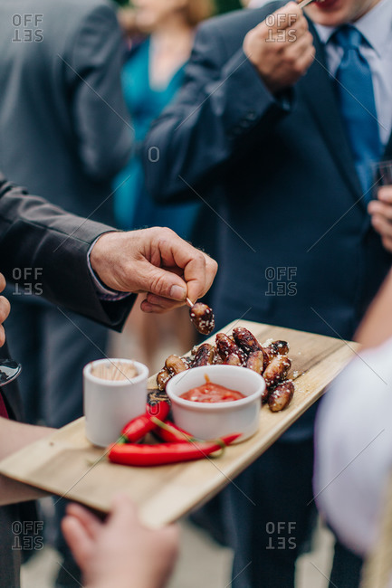 Man spears mini sausage with toothpick from serving tray