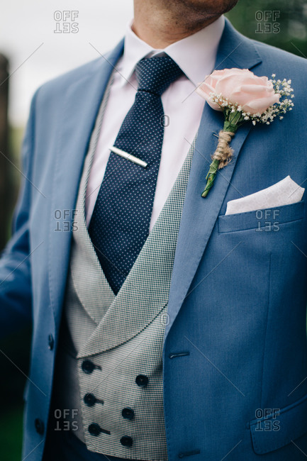 Closeup of groom in a blue jacket with rose boutonneire