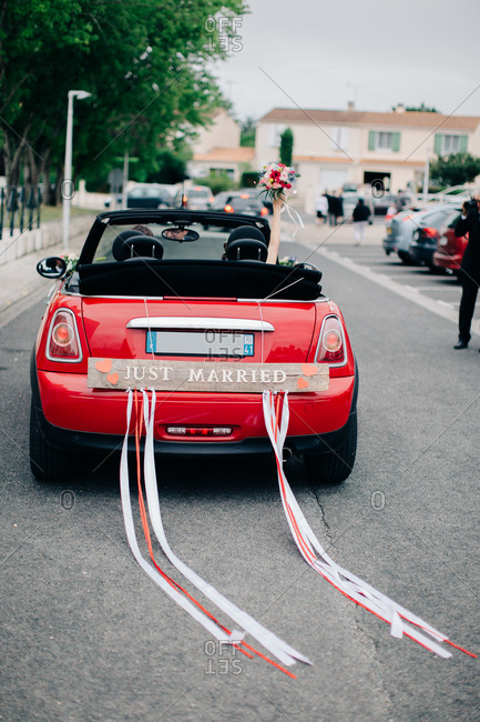 Bride and groom depart their wedding in red sport scar with Just Married sign