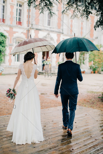 Back view of bride and groom walking under umbrellas outside chateau