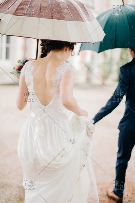 Bride lifting her dress while walking with umbrella in rain