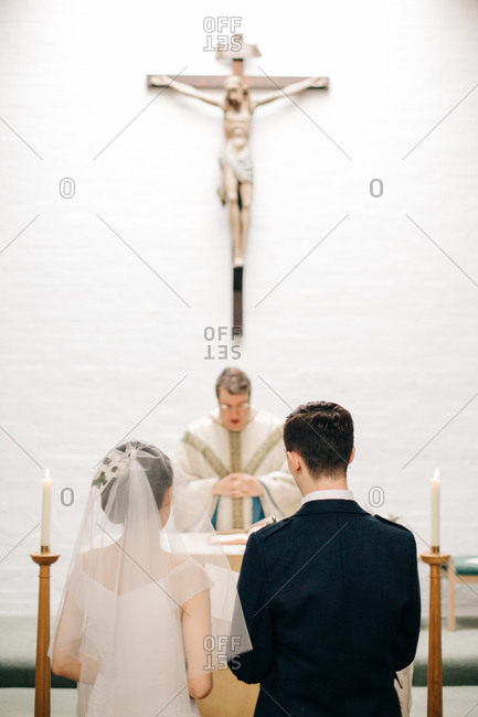 Bride and groom standing before pastor at altar in church