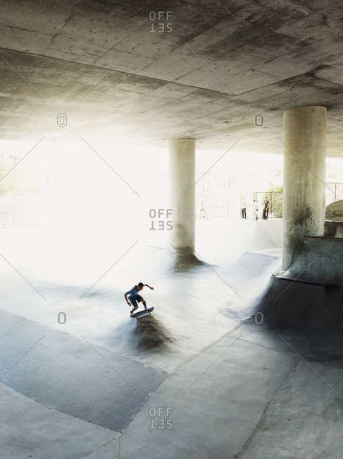 A man skates in San Diego skateboard park few people watch him from a vantage point