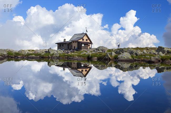 A solo hiker near the Rifugo Bernini, with reflections in a mountain lake