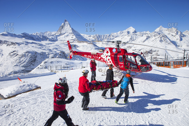 Zermatt, Wallis, Switzerland - February 11, 2014: Rescue personnel are carrying a litter with an injured skier to a helicopter