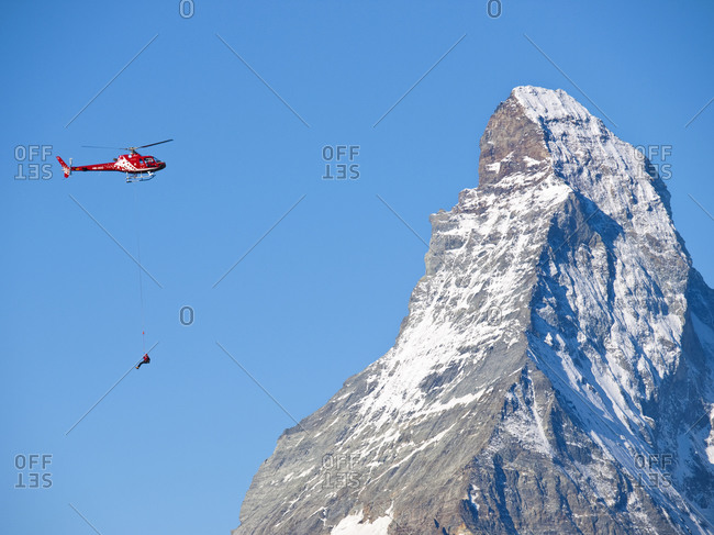 Zermatt, Wallis, Switzerland - August 16, 2011: A mountain rescue technician is dangling below a helicopter during a rescue mission in the Alps