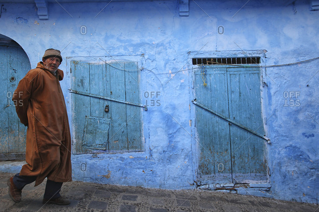 Chefchaouen, Morocco - December 1, 2013: Man walking on down a street