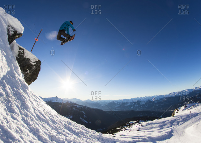 A snowboarder airs off a cliff by a ski resort boundary sign and grabs method above a mountainous horizon