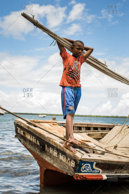 Lamu Island, Lamu, Kenya - October 11, 2013: A boy casually stands on the stern of an old wooden dhow sailboat in calm blue waters