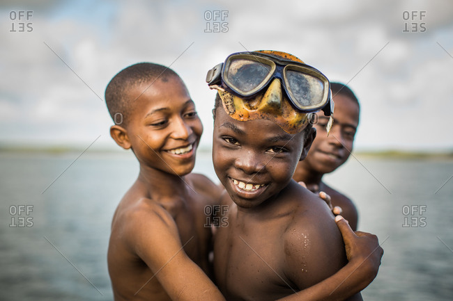 Lamu Island, Lamu, Kenya - October 11, 2013: Three young boys, one with old snorkel mask, huddle together, smiling after a swim