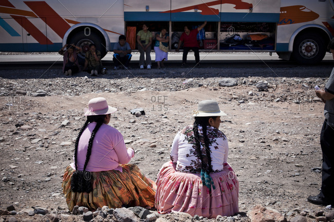 Salar de Uyuni, Bolivia - March 23, 2010: Two women wait on the side while their bus is repaired