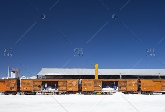 Salar de Uyuni, Bolivia - March 27, 2010: Workers load salt into trains