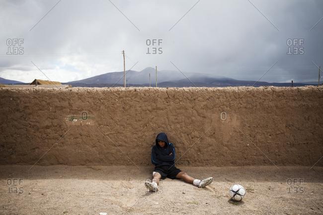 Salar de Uyuni, Bolivia - March 28, 2010: A soccer player rests against a wall in a small town near the Atacama Desert