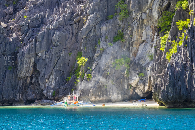 A couple embraces next to an outrigger boar anchored at a small beach on Tapiutan Island, El Nido, Palawan, Philippines