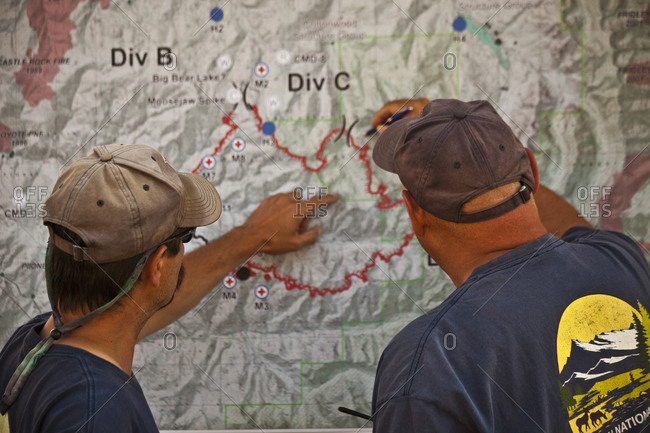 Two wild land firefighters look at a map in fire camp to decide the day's plan of attack