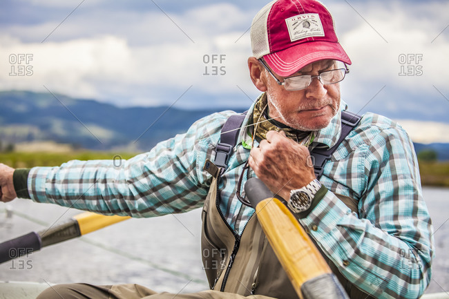 Montana, USA - June 19, 2014: A fly fisherman changes flies while on a drift boat on the Missouri River