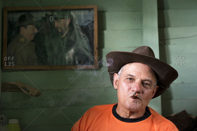Vinales, Cuba - May 13, 2015: Mariano, a tobacco farmer, smokes a cigar in the room of his house where he stores and hand rolls cigars