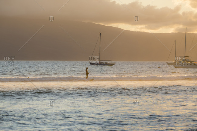 A solo surfer rides a long slow wave with sailboats and an island in the distance off the coast of Maui