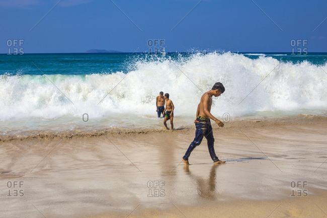 Kertasari, Sumbawa, Indonesia - October 19, 2014: Young boys playing near the ocean