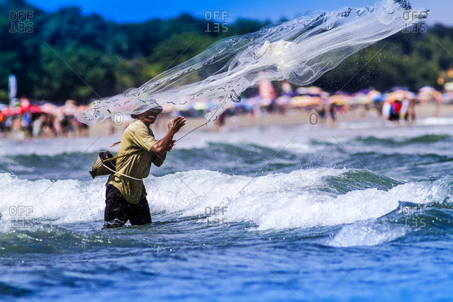 Kuta, Bali, Indonesia - July 21, 2013: Fisher man casting a net in the ocean